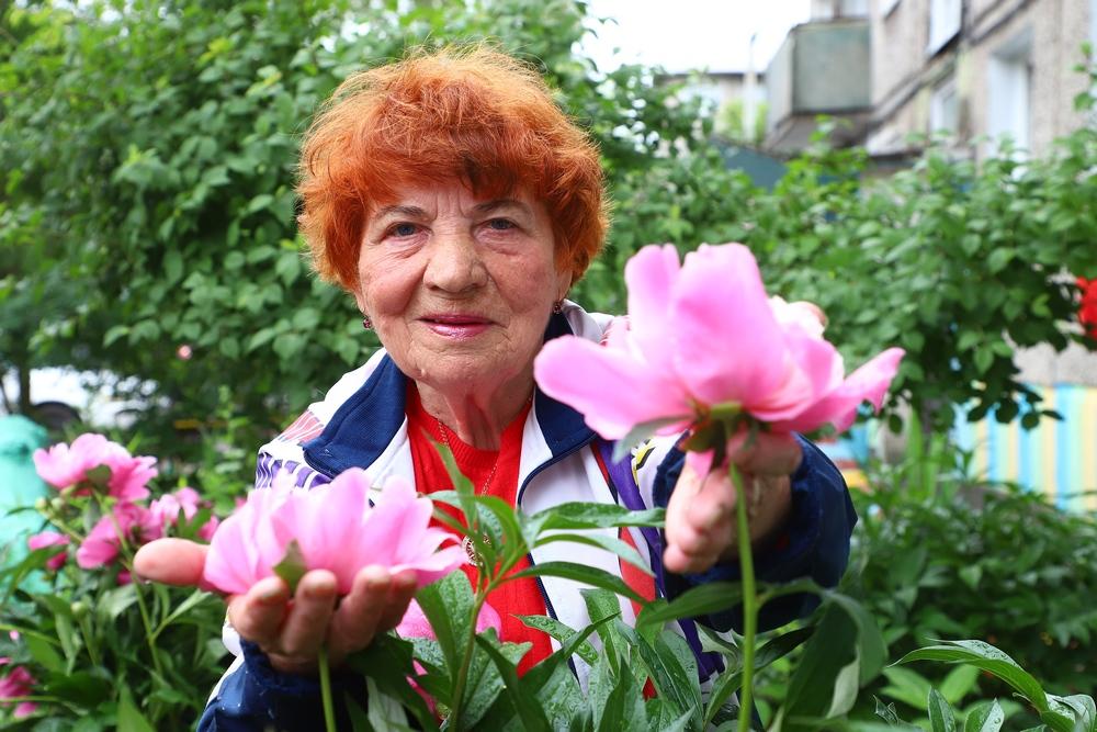 82-летняя жительница Красноярска разрисовала фасад пятиэтажки и высадила пионы возле подъезда